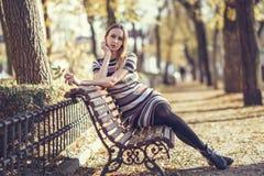 年轻白肤金发的妇女坐公园的长凳 免版税库存图片