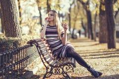年轻白肤金发的妇女坐公园的长凳 库存照片