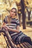 年轻白肤金发的妇女坐公园的长凳 免版税库存照片