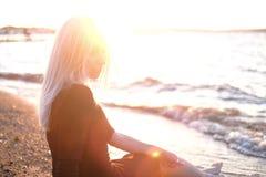 年轻白肤金发的妇女坐岸,日落光 库存照片