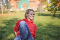 年轻白肤金发的妇女坐草在公园 她变冷  库存照片
