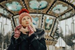 年轻白肤金发的妇女画象冬季衣服的 红色盖帽和手套 走在公园 库存照片