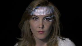 年轻白肤金发的妇女计算机程序设计者编制程序的画象,当二进制数据字符在她的面孔被射出-时 影视素材
