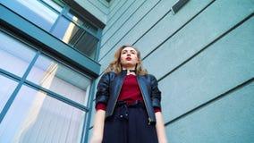年轻白肤金发的妇女身分低角度射击反对修造和打手势的 影视素材