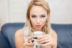 年轻白肤金发的妇女饮用的咖啡户内 库存照片