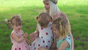 年轻白肤金发的嬉皮母亲有与她的女婴的质量时间在公园吹的蒲公英-女儿佩带相似 股票录像