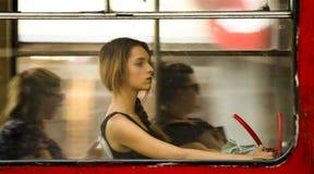 年轻白肤金发的少年妇女开会,当乘坐在靠窗座位时 免版税库存照片