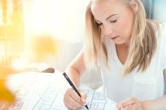年轻白肤金发的建筑师做计划 免版税库存图片