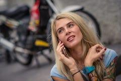年轻白肤金发的开会画象在摩托车的背景的 电话联系 有纹身花刺的女性手 库存照片