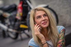 年轻白肤金发的开会画象在摩托车的背景的 电话联系 有纹身花刺的女性手 库存图片