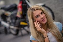 年轻白肤金发的开会画象在摩托车的背景的 电话联系 有纹身花刺的女性手 免版税库存图片