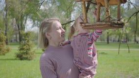 年轻白肤金发的母亲举行可爱的小女儿和在惊人的绿色公园显示她的鸟饲养者房子 妇女和孩子 股票视频
