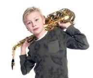 年轻白肤金发的男孩和萨克斯管在演播室 图库摄影