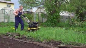 年轻白肤金发的肌肉农夫耕种与转台式微型翻土机的地面土壤 股票录像