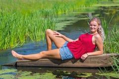 年轻白肤金发荷兰妇女说谎水面上本质上 免版税库存图片