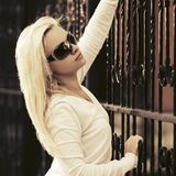 年轻白色套头衫和太阳镜的时尚白肤金发的妇女 图库摄影