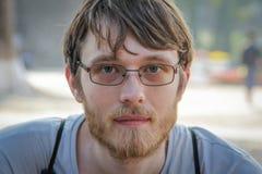年轻白色白种人男性白肤金发与轰隆和一个胡子与玻璃 库存照片