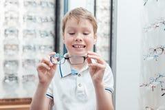 年轻的男孩非常满意对他新的镜片在商店 免版税图库摄影