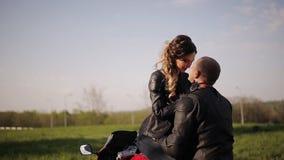 年轻皮夹克的坐摩托车亲吻在公园背景的人和女孩 股票视频