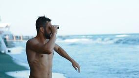 年轻看双筒望远镜海海滩夏天救生员救主赤裸赛跑游泳救星事故的体育可爱的人 股票视频