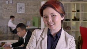 年轻看在照相机的企业亚裔妇女在现代办公室,微笑,黑和白种人供以人员工作  影视素材