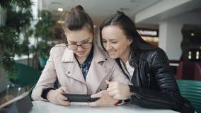 年轻看智能手机的母亲和青少年的女儿预期在咖啡馆的命令 秀丽青少年女孩使用 影视素材