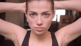 年轻看直接在健身房的照相机的适合运动员女性制造的ab锻炼特写镜头射击户内 股票录像