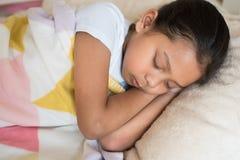 年轻矮小亚洲女孩睡觉说谎在床上在她的卧室 免版税库存照片