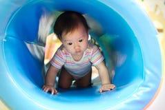年轻矮小的微笑的亚裔婴孩喜欢使用和爬行在蓝色管在孩子操场 库存图片