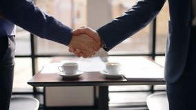 年轻确信的买卖人招呼,欢迎,握手在咖啡馆的桌上,两个人开正式会议 股票视频