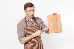 年轻确信的人厨师或侍者镶边棕色围裙的,拿着木切板,刀子的衬衣隔绝在白色 库存图片