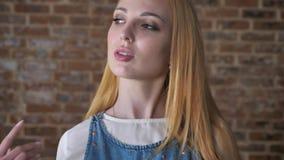 年轻确信的白肤金发的女孩观看在照相机,感人的头发,调情的人概念,砖背景 股票录像