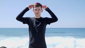 年轻确信的运动员离开他的站立在与后边波浪的海滩的太阳镜 r 股票录像