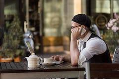 年轻程序员与膝上型计算机和电话一起使用在室外咖啡馆 库存照片