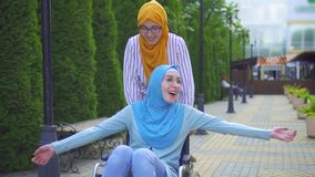 年轻穆斯林在一条传统围巾和玻璃失去了能力在获得的轮椅乐趣与一个回教朋友在街道上 股票视频