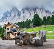 年轻穿着体面的人, 30-35,弹一把吉他有意大利白云岩岩层背景 免版税图库摄影