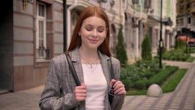 年轻站立在城市街道,看在照相机和拿着背包的鞔具姜俏丽的妇女,修造 股票视频