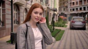 年轻站立在城市街道,看在照相机和接触她的头发的姜女学生,微笑,修造 股票录像