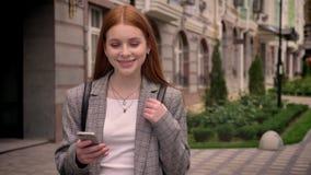 年轻站立在街道,看电话和秘密审议的姜迷人的妇女,拿着背包的鞔具,微笑 股票录像