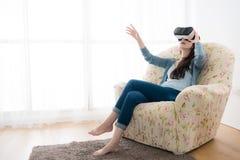 年轻端庄的妇女坐沙发椅子 免版税图库摄影