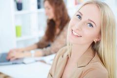 年轻笑的Cauicasian女实业家,有背景的女性同事的 事务和合作,工作 免版税库存图片