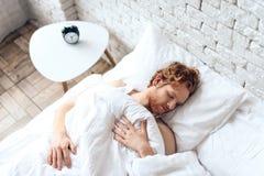 年轻红发人在床上睡觉 库存照片