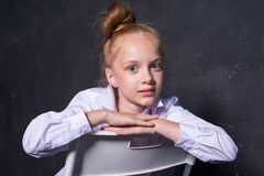 年轻红头发人女孩画象白色衬衣的在黑暗的背景 免版税图库摄影