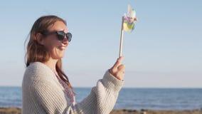 年轻红头发人妇女录影有轮转焰火玩具的在海 股票视频