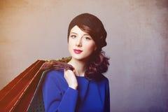 年轻红头发人妇女画象有购物袋的 图库摄影