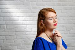 年轻红头发人妇女表情在砖墙上的 库存图片