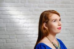 年轻红头发人妇女表情在砖墙上的 库存照片