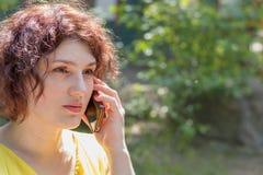 年轻红头发人妇女谈话在电话户外在一个晴天 免版税库存照片