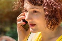 年轻红头发人妇女谈话在电话户外在一个晴天 图库摄影