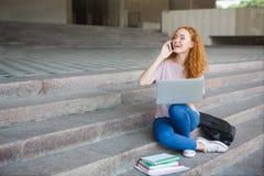 年轻红头发人学生女孩与膝上型计算机一起使用,谈话在手机,坐台阶户外 图库摄影
